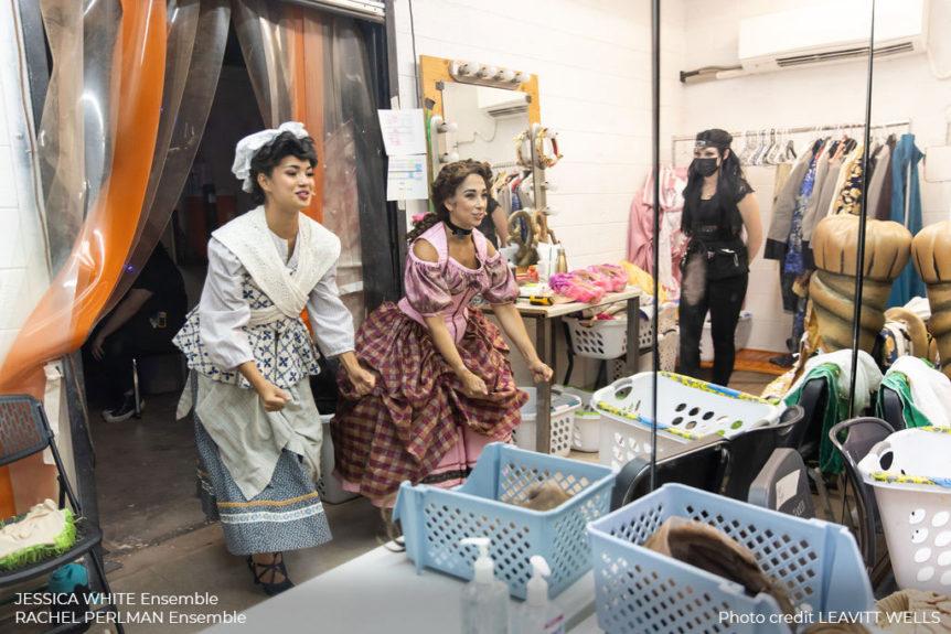 Jessica White and Rachel Perlman prepare as costume staff looks on.